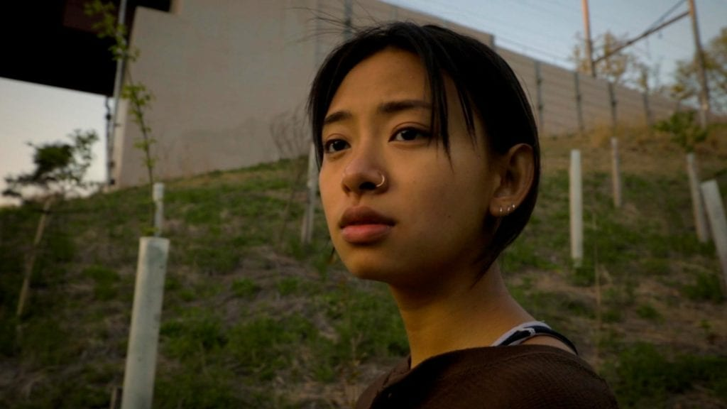 Mai gazes beyond the camera with a hill and bridge in the background